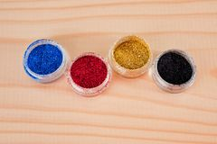 Multi-colored pearl glitter for manicure in jars taken on a wooden surface stock photo