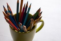 Multi-colored pencils in green cup on wooden white table background - front viewn royalty free stock photography