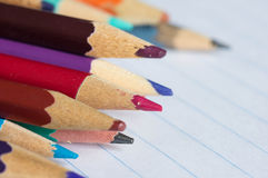 Multi-colored pencils on the writing-book page. Close up Stock Photos