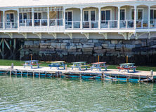 Multi Colored Picnic Tables on Pier Beneath Hotel Stock Image