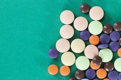 Multi-colored pills on a green background stock image