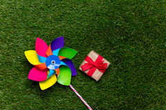 Multi colored pinwheel and little gift box on spring green glass Royalty Free Stock Photography