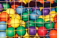 Multi-colored plastic balls for children`s maze behind grid. royalty free stock photo