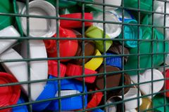 Multi-colored plastic screw caps from bottles behind an iron grid. Concept: waste management, environmental protection, separate stock images