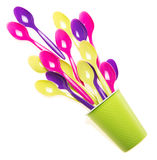 Multi-colored plastic spoons in the single cup isolated on white. Background royalty free stock photography