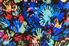 Multi-colored prints of hands smeared with paint on a black wall