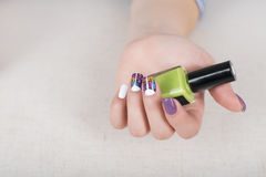Multi colored purple and white bright manicure. Multi colored purple and white manicure with polish in hand Stock Photography