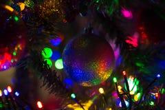 Multi-colored rainbow Christmas ball hanging on a Christmas tree