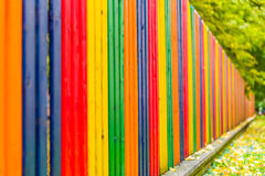 Multi colored rainbow wooden fence in autumn, garden background, soft focus, shallow depth of field Royalty Free Stock Images