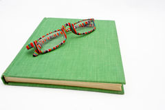 Multi-colored Reading Glasses and Old Book Royalty Free Stock Photography