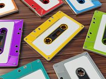 Multi-colored retro audio cassettes on wooden table. 3D illustration.  Stock Images