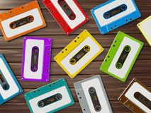 Multi-colored retro audio cassettes on wooden table. 3D illustration.  Stock Photography