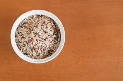 Multi colored rice on a white bowl. Wooden background Royalty Free Stock Images