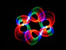 Multi-colored rings of light. Swirling multi-colored rings of light against a black background. They are blurred showing motion royalty free stock images