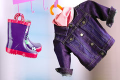 Multi-colored  rubber boots for kids hanging with jeans denim jacket Stock Photography