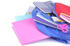 Multi-colored school supplies falling out of a backpack on a white isolated background royalty free stock images