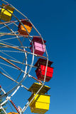 Multi Colored Seats in Ferris Wheel on Blue Sky Stock Photo