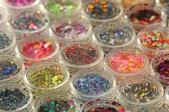 Multi colored Sequins for the design of nails in a Jar. Glitter in jars. Foil for nail service. Photo set. Sparkling beauty royalty free stock images
