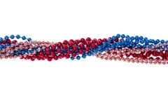 Multi colored shiny mardi gras beads on white background. Studio Photo royalty free stock photography