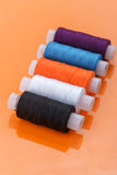 Multi-colored skeins of yarn. Several multi-colored skeins of yarn lying on orange glossy table Stock Images