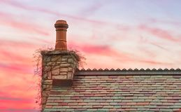 Multi Colored Slate Roof and Grape Vine Covered Chimney with a Spectacular Sunset. Old world colored shingles cover this roof of a cottage in the country side royalty free stock images