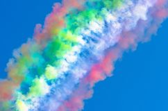Multi colored smoke in a blue sky. Multi colored smoke in a blue sky Royalty Free Stock Photo