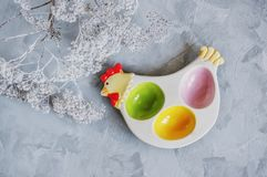 Multi-colored stand for Easter eggs on a white plate in the form of a chicken, top view. Copy space stock photography