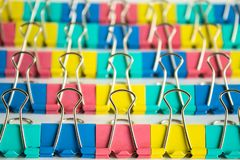 Multi-colored stationery clips in rows close-up on a neutral background stock image