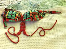 Swimsuit on a towel on the beach royalty free stock photography