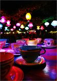 Multi Colored Tea Cups On Table Against Illuminated Lamps Hanging From Ceiling At Home Stock Photography