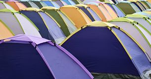 Multi colored tent city. Multi-colored tents organized in rows stock photos