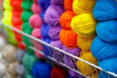 Multi-colored textile threads in hand-made reels are displayed for sale in the store stock photography