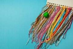 Multi-colored threads for embroidery homemade. Blue background stock photos