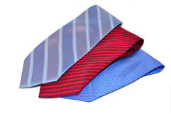 Multi Colored Ties on White Background. A set of three ties on top of one another, one blue with stripes, one red and one bright blue with design, all on a white royalty free stock photo