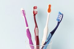 Multi-colored toothbrushes in a glass cup, blue background stock photos