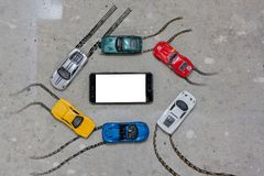 Multi Colored toy cars around a mobile phone top view stock images