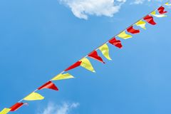 Multi colored triangular flags develop on the background of blue sky. Colorful fairground flags