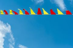 Multi colored triangular flags develop on the background of blue sky. Colorful fairground flags.