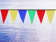 Multi Colored Triangular Flags Hanging against the backdrop of blue river. Stock Photo
