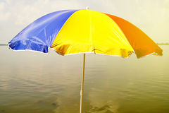 Multi-colored umbrella in the blue Lake and Sky Light shines Landscape Royalty Free Stock Photo