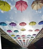Multi-colored umbrella hanging over the roof throughout the street on a beautiful blue day. N royalty free stock photo