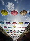 Multi-colored umbrella hanging over the roof throughout the street on a beautiful blue day. N stock images