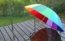Multi colored umbrella on wet wood planks Royalty Free Stock Image