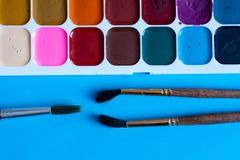 Multi-colored watercolor paints and brushes for drawing close-up on a blue background stock photo