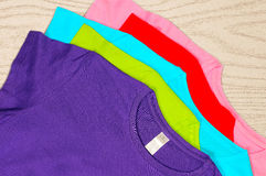 Multi-colored women's t-shirts lie on wooden background. Royalty Free Stock Photography