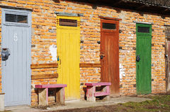 Multi colored wooden doors in the brick building Stock Image