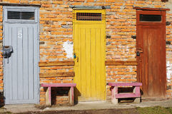 Multi colored wooden doors in the brick building Royalty Free Stock Image