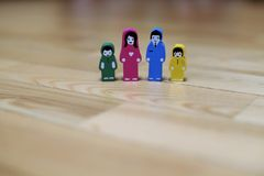 Multi-colored wooden figurines of a family with two children on a wooden floor background. parents together, children from differe Stock Photography