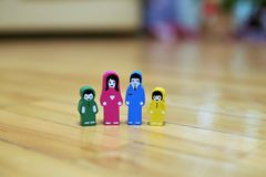Multi-colored wooden figurines of a family with two children on a wooden floor background. parents together, children from differe Stock Images