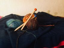 Multi-colored wool balls and wooden knitting needles, wool blankets royalty free stock image